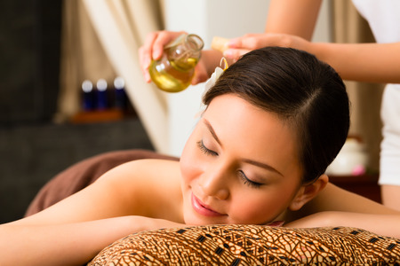 face massage: Chinese Asian woman in wellness beauty spa having aroma therapy massage with essential oil, looking relaxed