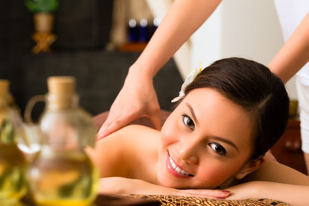 oil massage: Chinese Asian woman in wellness beauty spa having aroma therapy massage with essential oil, looking relaxed