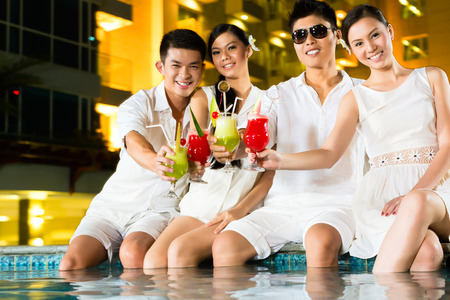 two couples: Two young and handsome Asian Chinese couples or friends drinking cocktails in a luxurious and fancy hotel pool bar