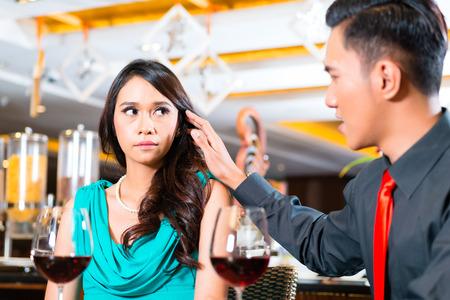stroking: Asian Man stroking girlfriends face in restaurant Stock Photo