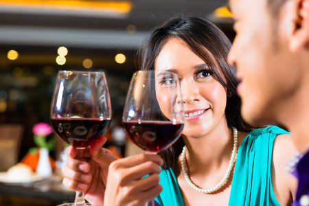 Close up of Asian couple toasting with red wine photo