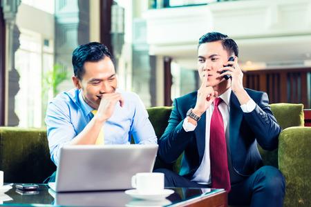hiss: Asian Businessman having a meeting and joking