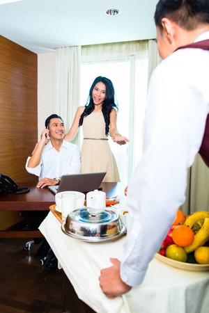 room service: Asian room service waiter serving breakfast in hotel room