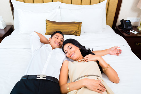 double beds: Asian couple lying on bed in hotel room Stock Photo