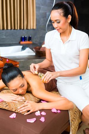 Beautiful Asian woman receiving massage photo