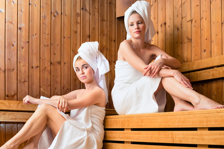 Two Women in sauna of wellness spa relaxing , enjoying an infusion photo