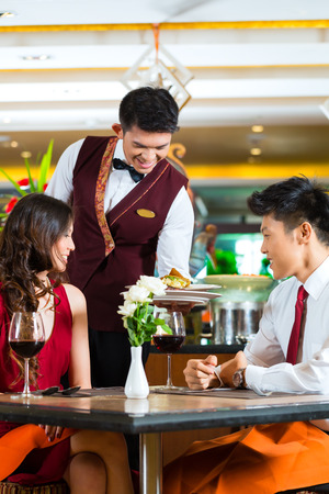 alcohol server: Asian Chinese couple - Man and woman - or lovers having a date or romantic dinner in a fancy restaurant while the waiter is serving food