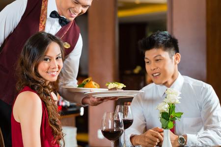 romantic dinner: Asian couple chinois - homme et femme - ou amateurs ayant une date ou un dîner romantique dans un restaurant chic tandis que le serveur est au service alimentaire