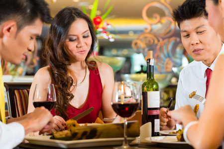dinner date: Two Asian Chinese Couples or friends or business people toasting during dinner or lunch in a elegant restaurant with red wine glasses