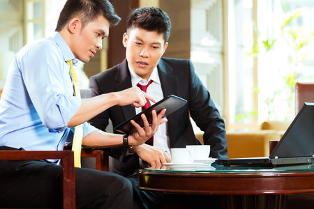 asian man: Two Asian Chinese businessman or office people having a business meeting in a hotel lobby discussing documents on a tablet computer while drinking coffee Stock Photo
