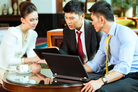 Three Asian Chinese office people or businessmen and businesswoman having a business meeting in a hotel lobby discussing documents on a tablet computer while drinking coffee Stock Photo