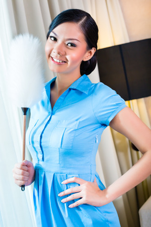 roomservice: Chambermaid dusting in Asian hotel room