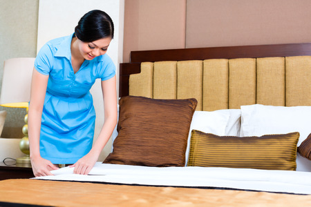 roomservice: Chambermaid making bed in Asian hotel room
