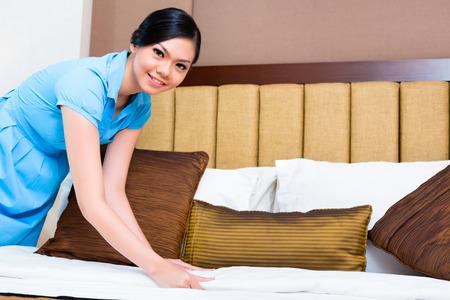 sirvienta: Camarera cama haciendo en la habitaci�n de hotel de Asia