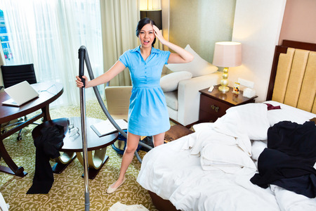 roomservice: Chambermaid cleaning in Asian hotel room