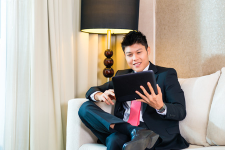 man in suite: Businessman in Asian hotel room working with tablet