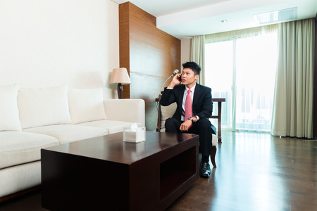 man in suite: Chinese Asian man with suit in business hotel suite working using phone sitting within his luxurious room
