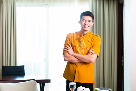 room service: Asian Chinese room service waiter or steward serving guests food in a grand or luxury hotel room