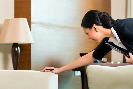 tidiness: Housekeeping manager or assistant controlling or checking the room or suit of a hotel with a checklist on tidiness Stock Photo