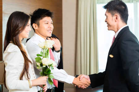 guest room: Asian Chinese Hotel Manager or director or supervisor welcome arriving VIP guests with roses on arrival in luxury or grand hotel