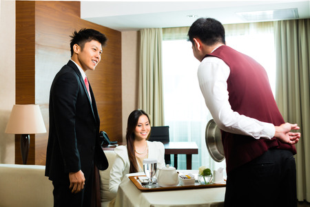 delivery room: Asian Chinese room service waiter or steward serving guests food in a grand or luxury hotel room