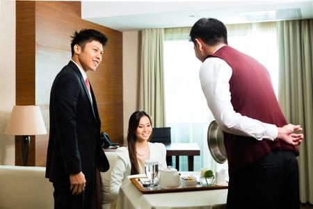 Asiatische chinesische Zimmerservice Kellner oder Verwalter Bedienung der Gäste Speisen in einem großen oder Luxus-Hotelzimmer Standard-Bild