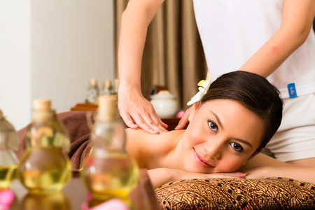 half body: Chinese Asian woman in wellness beauty spa having aroma therapy massage with essential oil, looking relaxed