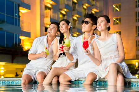lifestyle: Twee jonge en knappe Aziatische Chinese stelletjes of vrienden cocktails drinken in een luxe en chique bar van het hotel zwembad