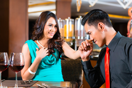 out of engagement: Asian couple sitting in restaurant Stock Photo