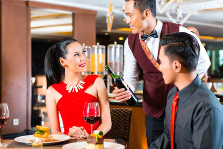 Young Asian couple dining in restaurant photo
