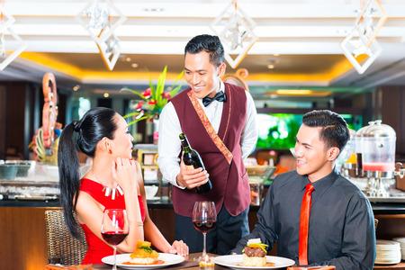 meseros: Camarero servir el vino en el restaurante asi�tico