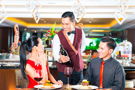 Waiter serving wine in Asian restaurant