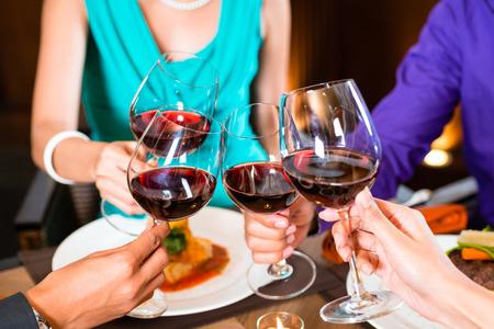 tomando vino: Cerca de las manos tostado en el restaurante asi�tico