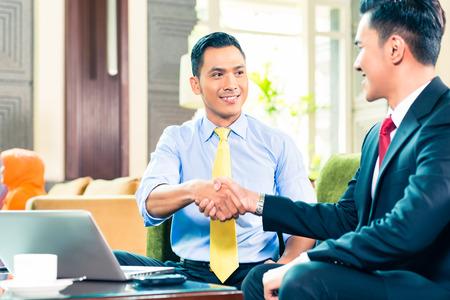 Aziatische zakenlieden handen schudden