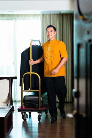 hotel indonesia: Portrait of bell boy pulling box van