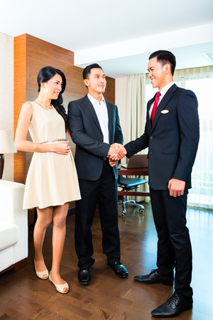 hotel staff: Manager greeting guests in hotel