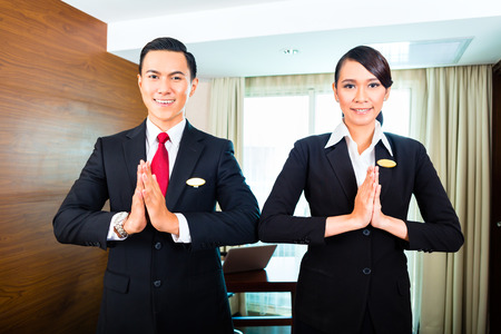 Portrait of hotel staff greeting with hands put together Stock Photo