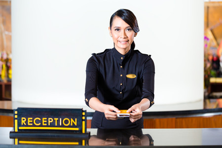 hotel service: Portrait of receptionist passing keycard in hotel