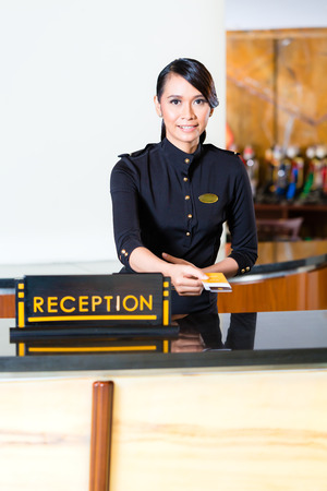 Portrait of receptionist passing keycard in hotel