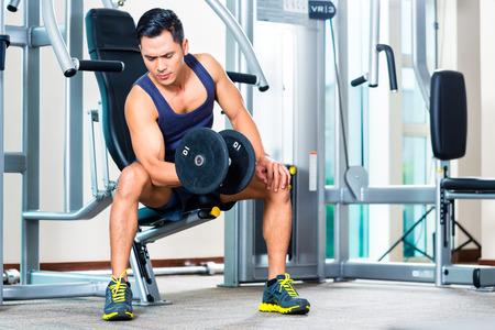 gimnasio: Asia peso de la mano de elevaci�n del hombre en el gimnasio
