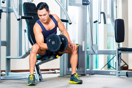 Asian man lifting hand weight at gym photo