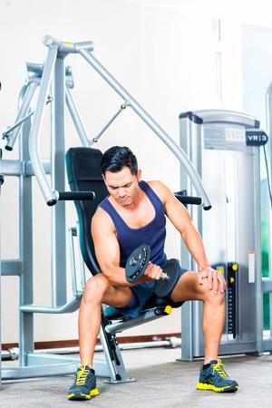 Asian man lifting hand weight at gym photo