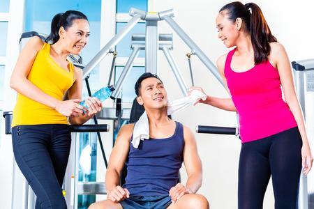 Women teasing man at gym photo