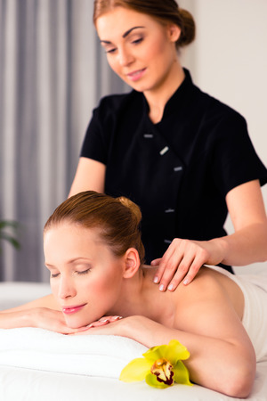 sensual massage: Massager giving woman in wellness beauty spa back massage with essential oil