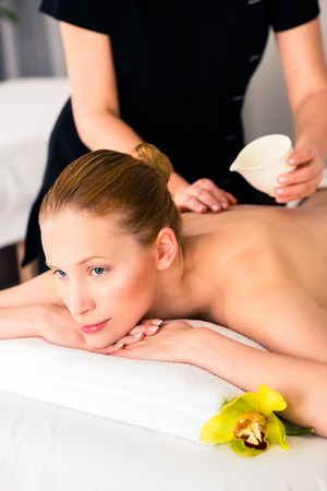 massage oil: Woman in wellness beauty spa having back massage with essential oil, looking relaxed