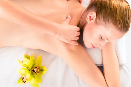 full face: Woman in wellness beauty spa having back massage with essential oil, looking relaxed
