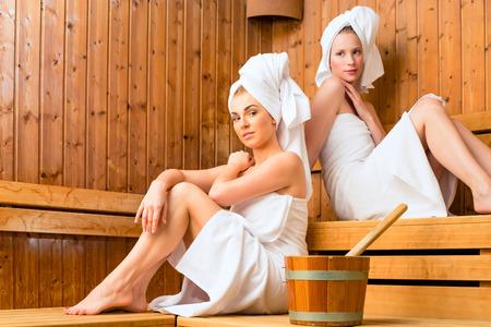 木製サウナでリラックスできるウェルネス スパで 2 人の女性
