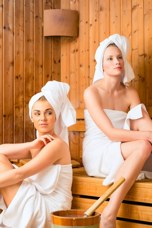Two Women in wellness spa relaxing in wooden sauna photo