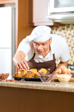 Asian man baking homemade cup cake muffins in his kitchen for dessert Stock Photo