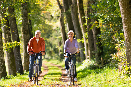 Senior Man and woman exercising with bicycles outdoors, they are a couple Foto de archivo